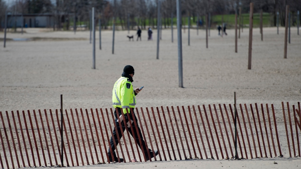 A City of Toronto by-law officer walks on Woodbine Beach with his ticket book making sure people are practicing physical distancing in Toronto on Friday, April 10, 2020. Health officials and the government have asked that people stay inside to help curb the spread of COVID-19. THE CANADIAN PRESS/Nathan Denette