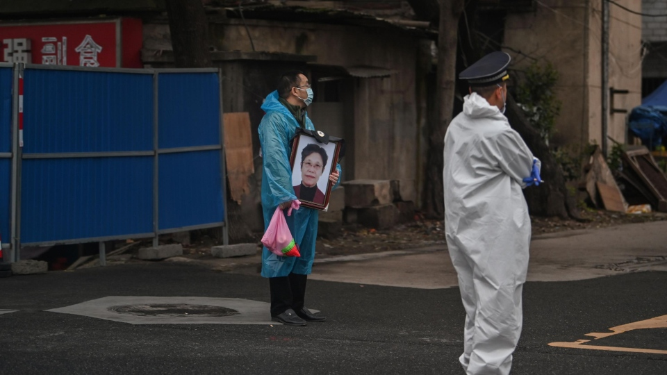 A man wearing a mask and a blue raincoat holds a portrait as he stands outside the Biandanshan cemetery in Wuhan on March 31. (HECTOR RETAMAL/AFP/AFP via Getty Images)