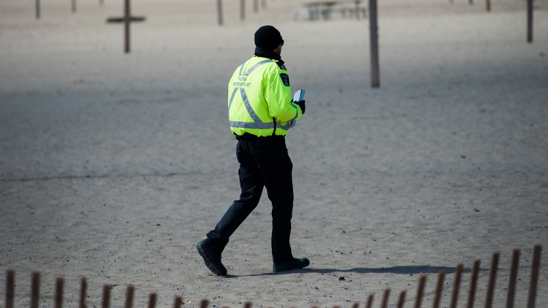A City of Toronto by-law officer walks on Woodbine Beach with his ticket book making sure people are practicing physical distancing in Toronto on Friday, April 10, 2020. Health officials and the government have asked that people stay inside to help curb the spread of COVID-19. (Nathan Denette/The Canadian Press)