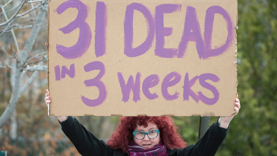 A woman holds up a sign outside Maison Herron, a long term care home in the Montreal suburb of Dorval, Que., on Saturday, April 11, 2020, as COVID-19 cases rise in Canada and around the world. THE CANADIAN PRESS/Graham Hughes