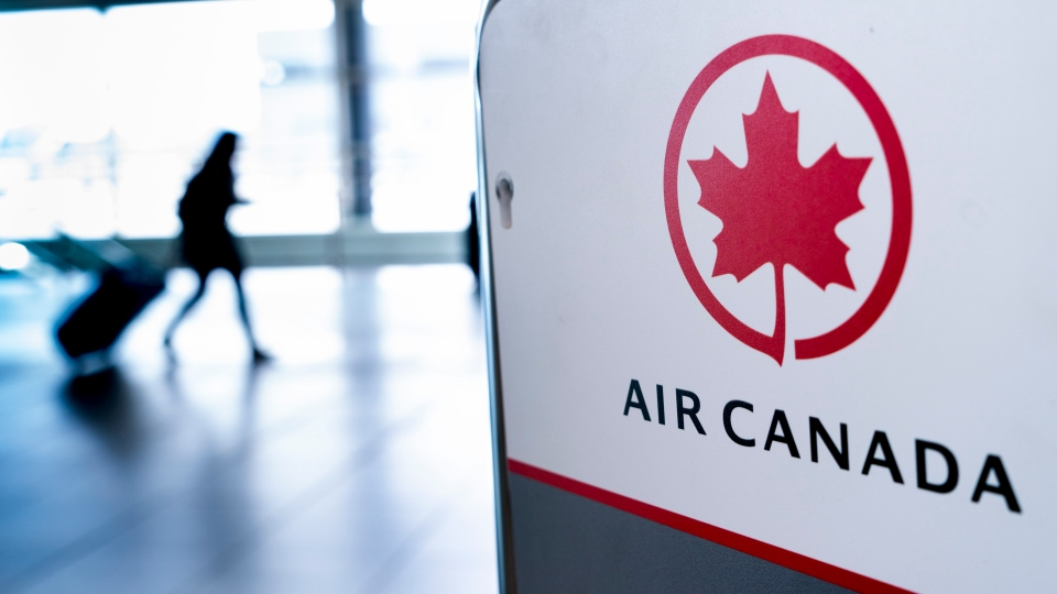 A lone passenger walks past the Air Canada check-in counter at Montreal-Trudeau International Airport in Montreal, on Wednesday, April 8, 2020. (THE CANADIAN PRESS/Paul Chiasson)