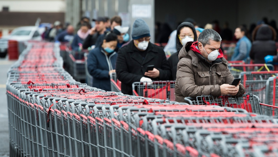 Hundreds of people wait in line to enter Costco in Toronto on Monday, April 13, 2020. Health officials and the government have asked that people stay inside to help curb the spread of COVID-19. THE CANADIAN PRESS/Nathan Denette