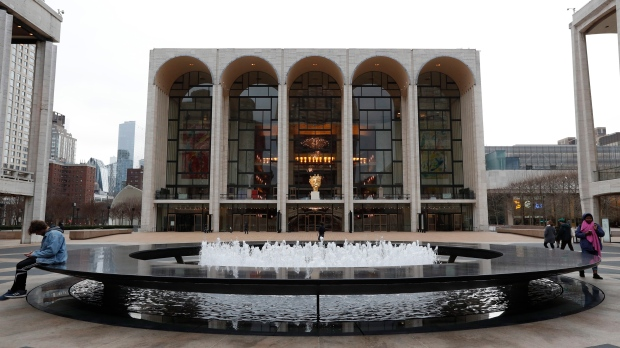 This March 12, 2020 file photo shows a few people at Josie Robertson Plaza in front of The Metropolitan Opera house, background center, at Lincoln Center in New York. (AP Photo/Kathy Willens, File)