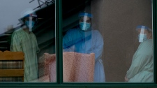 Healthcare workers look out from Maison Herron, a long term care home in the Montreal suburb of Dorval, Que., on Saturday, April 11, 2020, as COVID-19 cases rise in Canada and around the world. (THE CANADIAN PRESS/Graham Hughes)