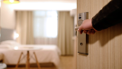 A man opens the door to a hotel room.