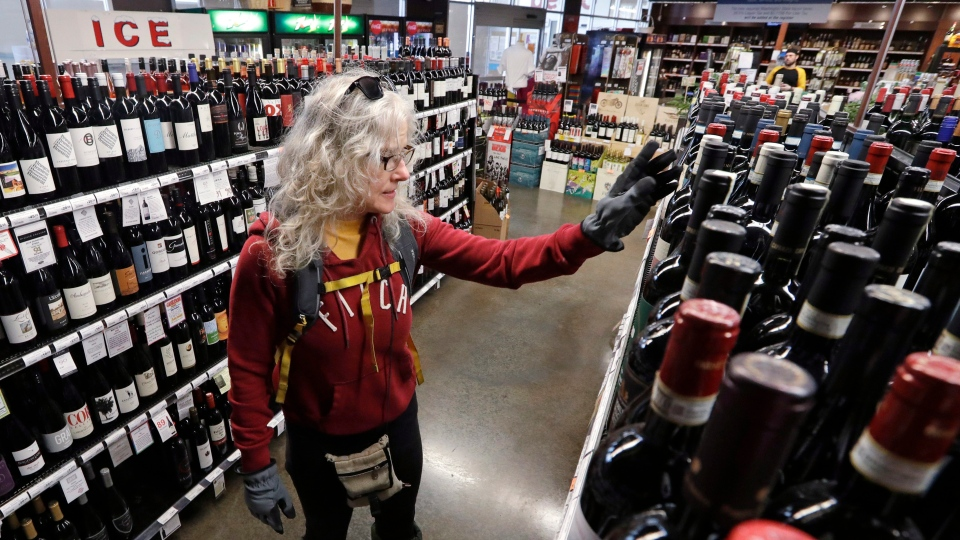 In this photo taken Wednesday, March 25, 2020, Lisa MacDonald shops for wine in a liquor store in Seattle. (AP Photo/Elaine Thompson)