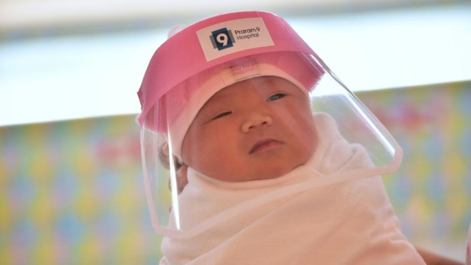A newborn wearing a face shield