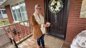 Lynne Spencer stand outside her Bryson, QC home with Sammy the gecko. April 16, 2020. (Tyler Fleming / CTV News Ottawa)