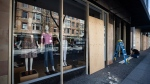 A worker boards up a closed clothing store in Vancouver, on Thursday, April 16, 2020. THE CANADIAN PRESS/Darryl Dyck
