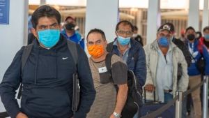 Migrant workers from Mexico maintain social distancing as they wait to be transported to Quebec farms after arriving at Trudeau Airport Tuesday April 14, 2020 in Montreal. THE CANADIAN PRESS/Ryan Remiorz