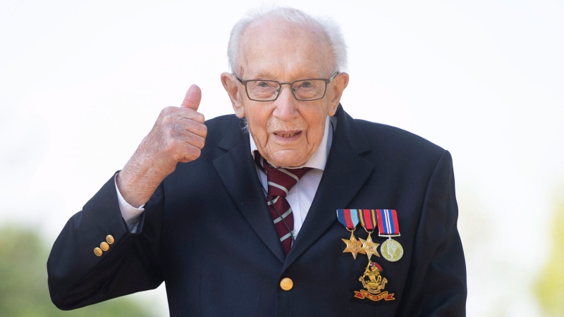 99-year-old war veteran Captain Tom Moore, poses for a photo at his home in Marston Moretaine, England, after he achieved his goal of 100 laps of his garden, raising millions of pounds for the NHS with donations to his fundraising challenge from around the world, Thursday April 16, 2020. (Joe Giddens/PA via AP)