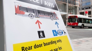 A bus passes a sign indicating users should enter the bus by the rear door as part of COVID-19 measures in Ottawa, Thursday April 16, 2020. (Adrian Wyld/THE CANADIAN PRESS)