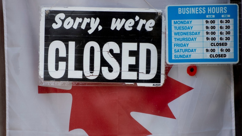 A 'Closed' sign hangs in a store window in Ottawa