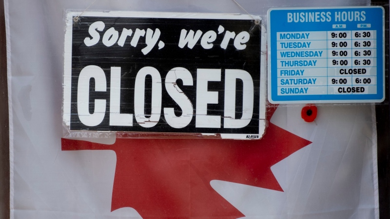 A 'Closed' sign hangs in a store window in Ottawa, Thursday April 16, 2020. (Adrian Wyld/THE CANADIAN PRESS)
