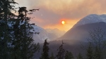 Smoke from a wildfire hangs over the mountains in Squamish, B.C., Wednesday, April 15, 2020. (Amy Smart / The Canadian Press)