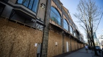 Boarded up clothing stores are seen on Robson Street, in Vancouver, on Thursday, April 16, 2020. (Darryl Dyck / THE CANADIAN PRESS)