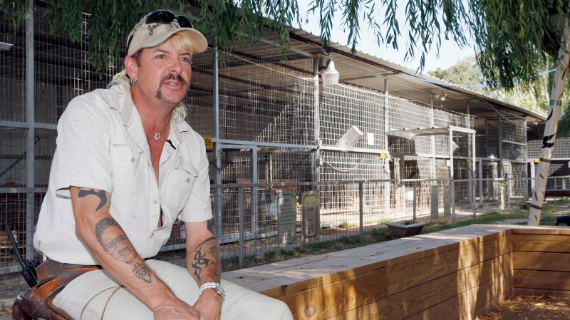 "In this Aug. 28, 2013, file photo, Joseph Maldonado answers a question during an interview at the zoo he runs in Wynnewood, Okla. Federal prosecutors on Friday, Sept. 7, 2018, announced that the zookeeper, also known as ""Joe Exotic,"" and candidate for governor earlier this year, has been charged in a murder-for-hire scheme alleging he tried to hire someone to kill a Florida woman. Prosecutors allege Maldonado-Passage tried to hire two separate people to kill the woman, who wasn't harmed. Maldonado-Passage finished third in a three-way Libertarian primary in June. (AP Photo/Sue Ogrocki, File)"