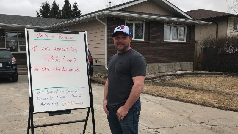 "Graeme Parsons stand by his ""pun-demic"" white board in his driveway. (Stefanie Davis/CTV News)"