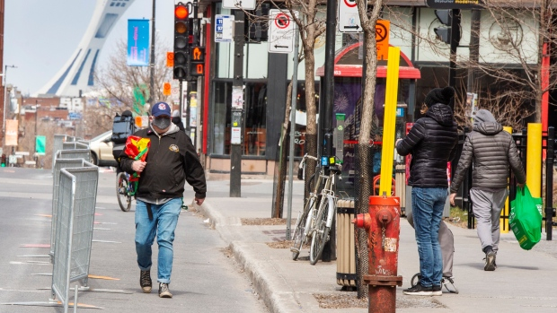 Pedestrians practice social distancing as the city widens sidewalks by closing a lane to cars Friday April 17, 2020 in Montreal. THE CANADIAN PRESS/Ryan Remiorz