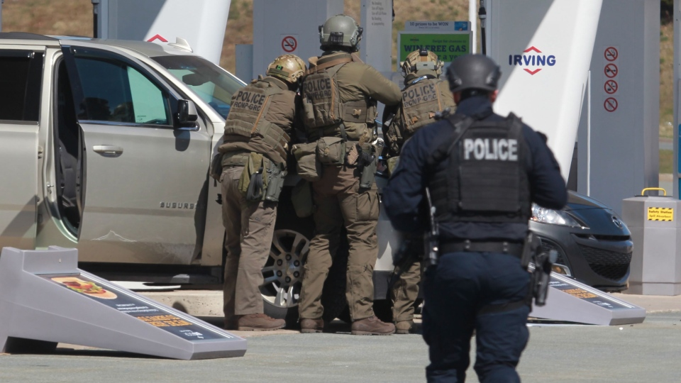 RCMP officers prepare to take a person into custody at a gas station in Enfield, N.S. on Sunday April 19, 2020. (THE CANADIAN PRESS/Tim Krochak)