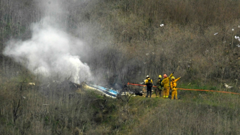 In this Jan. 26, 2020, file photo, firefighters work the scene of a helicopter crash where former NBA basketball star Kobe Bryant died in Calabasas, Calif. (AP Photo/Mark J. Terrill)