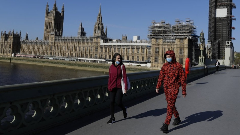 People wear masks as they walk near Britain's Houses of Parliament as the country is in lockdown to help curb the spread of coronavirus, in London, Tuesday, April 21, 2020. (AP Photo/Kirsty Wigglesworth)