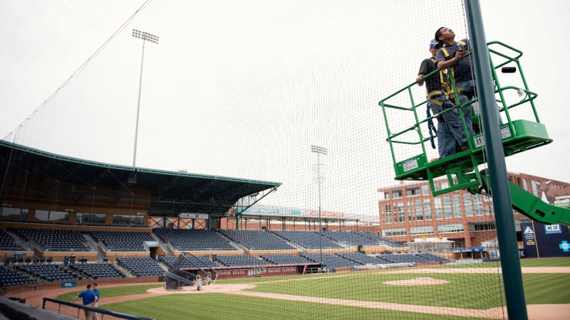 Installing safety netting behind home plate and along the length of each dugout at the Durham Bulls Athletic Park in Durham, N.C., on March 31, 2016.  (Whitney Keller/The Herald-Sun via AP, File)