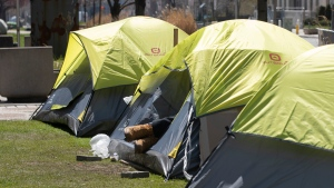 A homeless person lies in a tent pitched in a centre reservation in downtown in Toronto on Saturday, April 18, 2020. (THE CANADIAN PRESS / Chris Young)