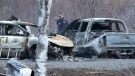 An RCMP investigator inspects vehicles destroyed by fire at the residence of Alanna Jenkins and Sean McLean, both corrections officers, in Wentworth Centre, N.S. on Monday, April 20, 2020. THE CANADIAN PRESS/Andrew Vaughan