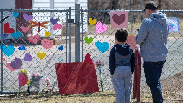 A man and his son pay respects at a memorial to Lisa McCully, a teacher at Debert Elementary School in Debert, N.S. on Tuesday, April 21, 2020. THE CANADIAN PRESS/Andrew Vaughan