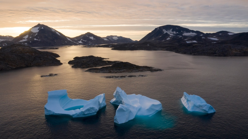 In this Aug. 16, 2019, photo, large Icebergs float away as the sun rises near Kulusuk, Greenland. (AP Photo/Felipe Dana, File)