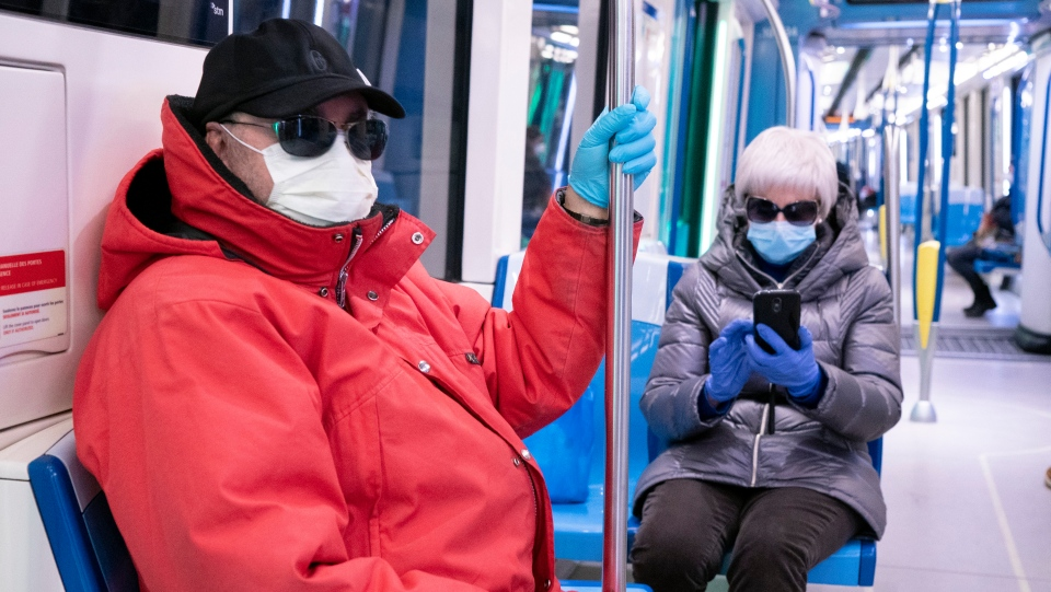 A couple wearing a protective masks ride a near empty subway train in Montreal, on Wednesday, April 22, 2020. THE CANADIAN PRESS/Paul Chiasson
