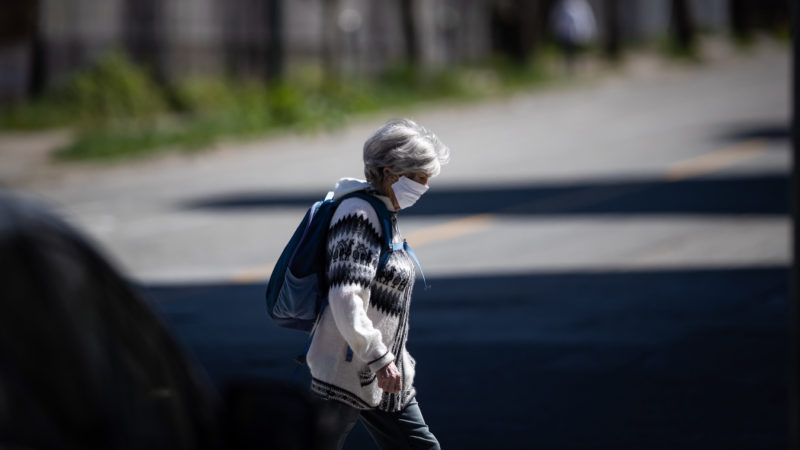 A woman wearing a fabric mask on her face walks in downtown Vancouver, on Thursday, April 16, 2020. Infectious disease experts say provinces looking to relax restrictions related to COVID-19 need to consider their neighbours in those decisions. THE CANADIAN PRESS/Darryl Dyck