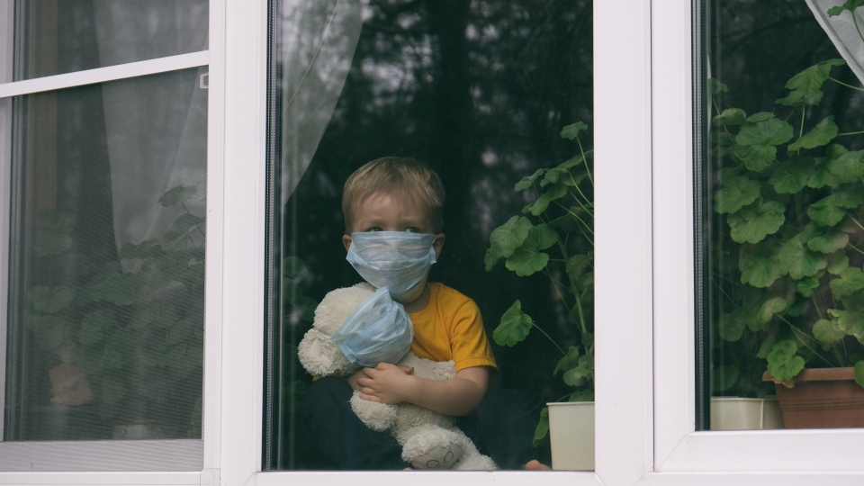 A child is seen wearing a face mask. (Shutterstock)