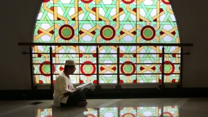 A man reads the Quran at a mosque during Ramadan (file photo taken before the pandemic). With Quebec's curfew rolled back to 8 p.m. in Montreal and Laval, many in Quebec won't be able to attend evening prayer. (AP / Tatan Syuflana)