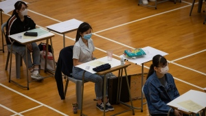 Students wearing masks to help stop the spread of the new coronavirus, sit for the Diploma of Secondary Education (DSE) exams at a school in Hong Kong, Friday, April 24, 2020. (Jerome Favre/Pool Photo via AP)