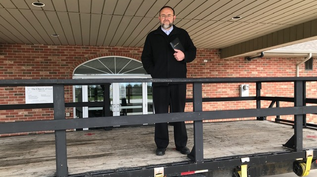 Pastor Henry Hildebrandt of the Church of God in Alymer, Ont. stands on a platform placed in front of his church utilized to deliver his sermon on Friday, April 24, 2019. (Sean Irvine / CTV London)