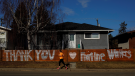 A jogger runs past a sign thanking frontline workers during the COVID-19 pandemic, in Edmonton on Friday, April 24, 2020. THE CANADIAN PRESS/Jason Franson