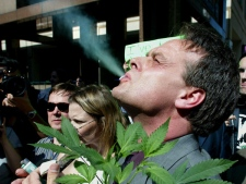 Cannabis crusader Marc Emery, of Vancouver, smokes marijuana as he holds a plant at a gathering of pro-marijuana legalization supporters outside police headquarters in Toronto June 19, 2003. (CP / Kevin Frayer)