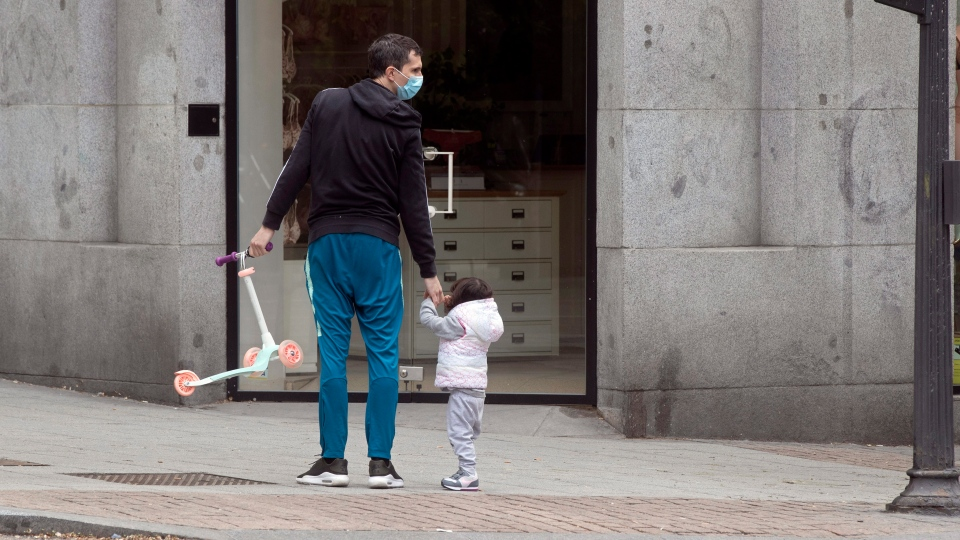 A man takes a young girl for a walk in Madrid, Spain, Sunday, April 26, 2020. On Sunday, children under 14 years old are allowed to take walks with a parent for up to one hour and within one kilometer from home, ending six weeks of compete seclusion due to the coronavirus outbreak. (AP Photo/Paul White)