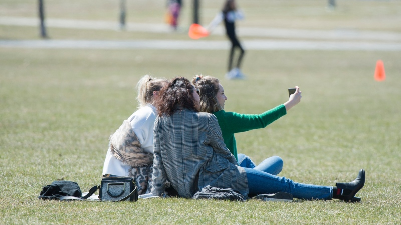 Women take a photograph in a park in Montreal, Saturday, April 25, 2020, as COVID-19 cases rise in Canada and around the world. THE CANADIAN PRESS/Graham Hughes