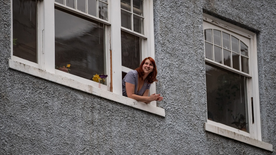 A woman applauds from the upper floor window of an apartment in support of healthcare workers, along with many others on balconies at 7 p.m. in Vancouver's West End, on Monday, March 23, 2020. (THE CANADIAN PRESS / Darryl Dyck)