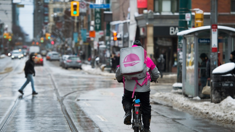 A Foodora courier is pictured as they pick up an order for delivery from a restaurant in Toronto, Thursday, Feb. 27, 2020. (THE CANADIAN PRESS / Nathan Denette)