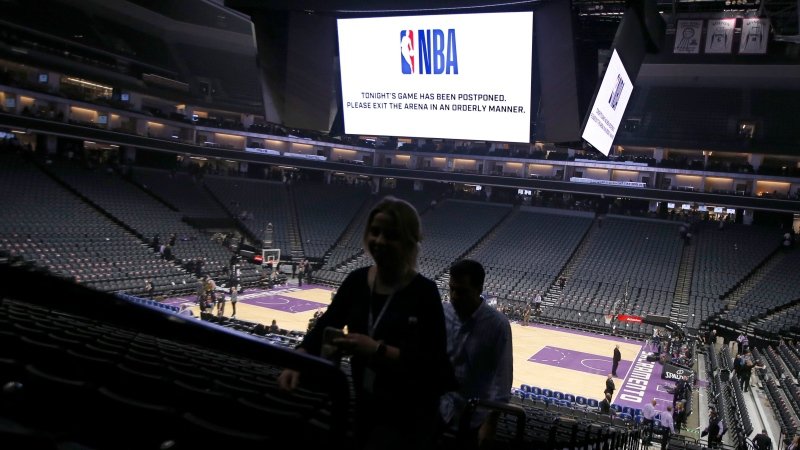 "In this March 11, 2020 photo, fans leave the Golden 1 Center in Sacramento, Calif., after the NBA basketball game between the New Orleans Pelicans and Sacramento Kings was postponed at the last minute over an ""abundance of caution"" after a player for the Jazz tested positive for the coronavirus. (AP Photo/Rich Pedroncelli, File)"