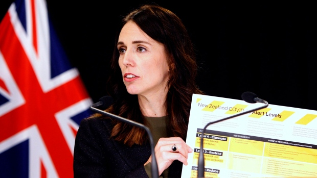 In this March 21, 2020, file photo, New Zealand Prime Minister Jacinda Ardern holds up a card showing a new alert system for COVID-19 in Wellington, New Zealand. (AP / Nick Perry, File)