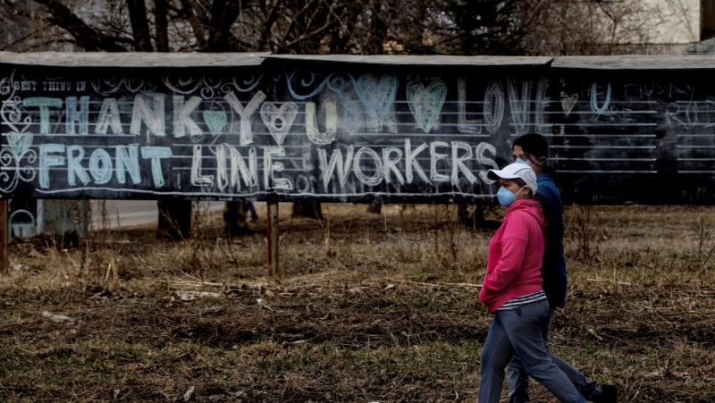 Pedestrians in masks walk past a chalk sign thanking front-line workers, during the COVID-19 pandemic, in Edmonton on Thursday, April 23, 2020. THE CANADIAN PRESS/Jason Franson