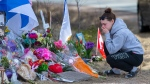 A woman pays her respects at a roadside memorial on Portapique Road in Portapique, N.S. on Friday, April 24, 2020. (Courtesy: THE CANADIAN PRESS/Andrew Vaughan)
