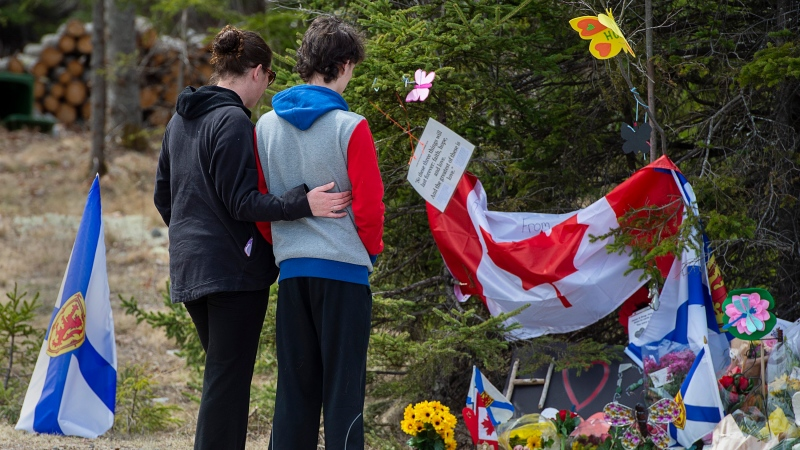 Visitors to a roadside memorial pays their respects in Portapique, N.S. on Friday, April 24, 2020. (Courtesy: THE CANADIAN PRESS/Andrew Vaughan)