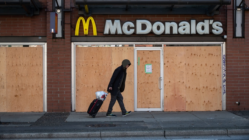 A man walks past a McDonald's restaurant with boarded up windows that has been closed due to the coronavirus, in the Downtown Eastside of Vancouver, on Wednesday, March 25, 2020. (THE CANADIAN PRESS / Darryl Dyck)