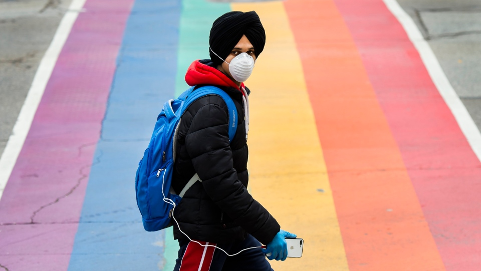 A man wearing a mask crosses the street during the COVID-19 pandemic in Toronto on Tuesday, April 28, 2020. THE CANADIAN PRESS/Nathan Denette